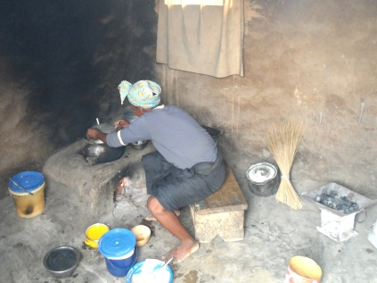 A woman prepares food on an energy-saving mud stove. She learned how to construct the stove during participatory training with Trax Ghana