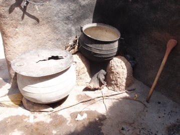 A traditional local mud stove which has open sides so burns more fire wood